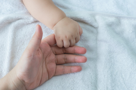 baby curling his finger around parent finger